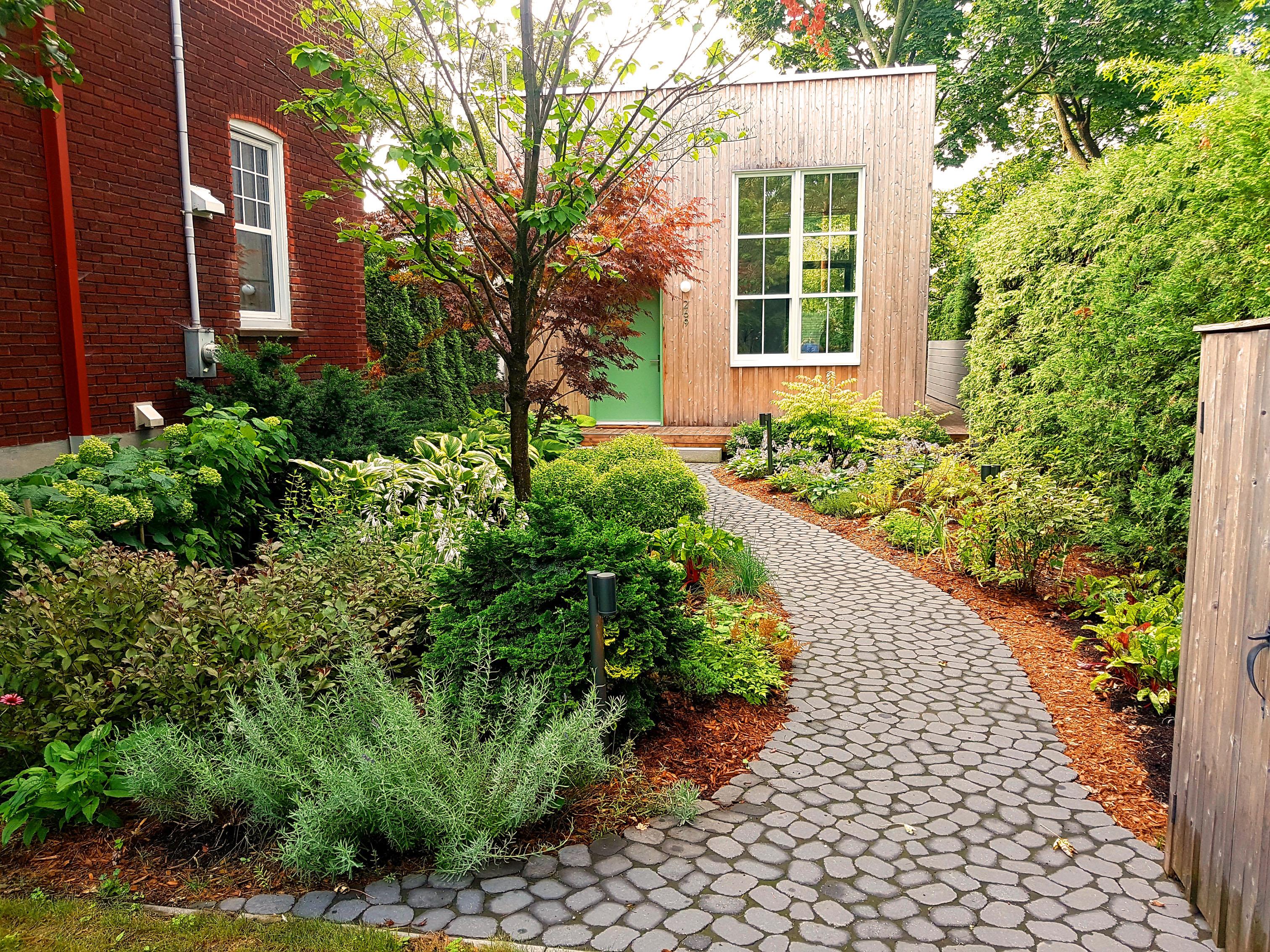 Traitement paysager d'une maisonnette comme s'il s'agissait d'une maison de campagne en milieu urbain, allée gourmande incluse! (Légumes et Fines herbes sont dissimulés parmi les plantes ornementales..)