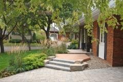 Approche d'entrée réinventée, combinant le pavé, la pierre et le bois, rendant l'expérience d'accès plus enrichissante.